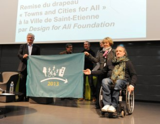 Participants on stage holding Flag at ceremony in Saint-Étienne