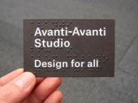 Photo of hand holding Avant-Avanti business card, which reads 'Avanti-Avanti Studio Design for all' in white letters on dark-brown background and Braille text